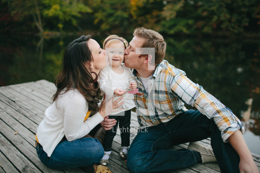 Mother and Father kissing their daughter.