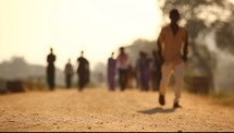 men and women walking down a dirt road