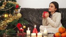 a gift drinking from a mug sitting on a couch near a Christmas tree