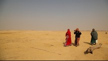 women covered in scarves walking through the desert