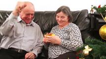 Elderly couple talking near a Christmas tree