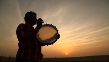 man playing a tambourine at sunset