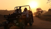 men in a Jeep on a dirt road in India at sunset