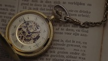 pocket watch on the pages of a Bible