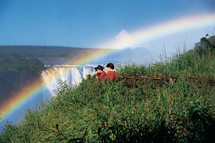People viewing a rainbow over a waterfall