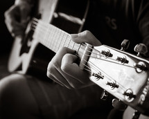 hand on the neck of a guitar