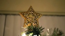 gold star on the top of a Christmas tree