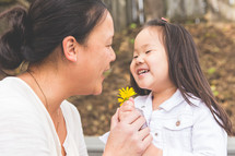 girl child giving mother picked flowers for mother's day