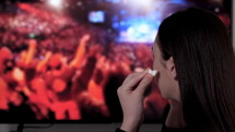 Young woman using wireless earbuds in her ears and listening to a concert on TV. Worship concert. Audio technology concept.