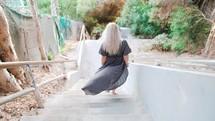 a woman walking down steps in a flowing dress