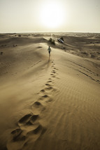 man running on sand dunes in a desert in Dubai