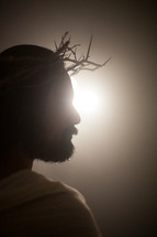 Jesus with a crown of thorns surrounded by a glowing light