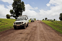White sports utility vehicles travel down a remote dirt road.