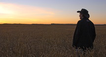 A man wearing a cowboy hat watches the sunrise in a wheat field. A