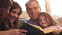 grandparents reading a Bible with their grandkids