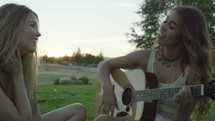 friends sitting on a blanket in the grass playing the guitar and singing
