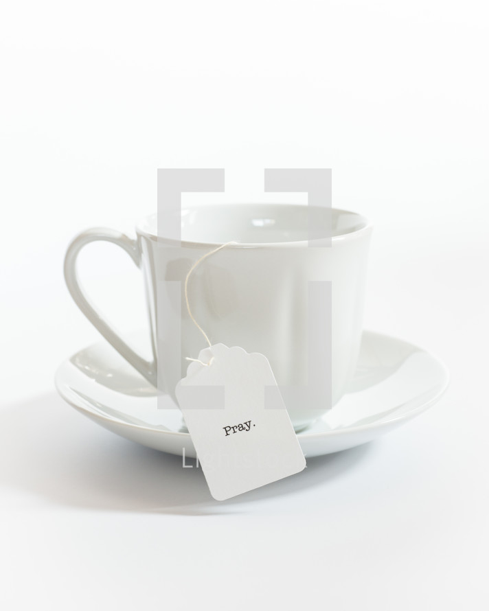 tea cup with the word pray on the tea bag