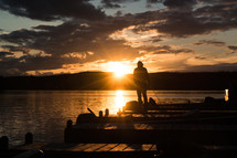 a man on a dock at sunset