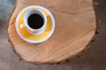 coffee cup and saucer on a cut wood table