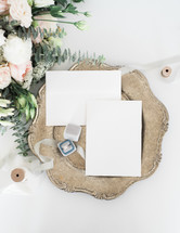 envelopes on a silver tray and engagement ring