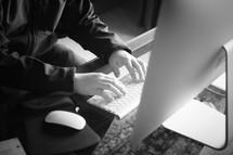 a man typing at his desk