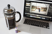 coffee press and laptop opened to wedding photos