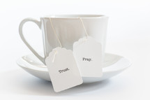 tea cup with the words trust and pray on the tea bag