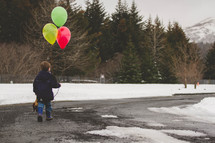 boy child walking in snow carrying a stuffed animal and balloons