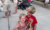 two children with colorful hair at an outdoor summer festival