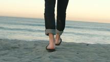 man in flip flops walking on a beach