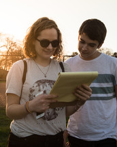 two teens reading a notepad outdoors
