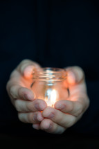 Hands holding a jar with a burning candle.