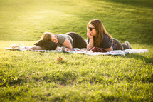 friends lying on a blanket in the grass