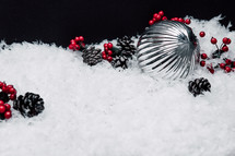 pine cones, red berries, ornaments, and snow