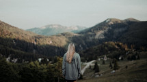 a woman standing with her back to the camera looking out at mountains
