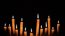 flickering flames on candles in darkness