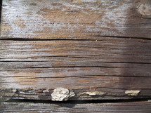 A close-up photograph of weathered and old wood grain showing the age and texture of a piece of wood such as an old wooden cross.