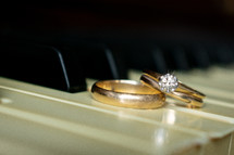 gold wedding rings on a piano