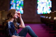 Young woman or teen sitting in aisle of a church with a joyful smile.