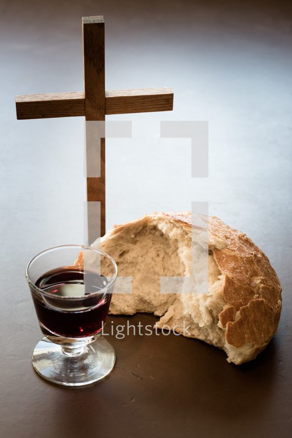bread and wine on a cutting board and cross
