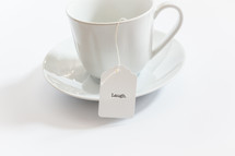 tea cup with a tea bag with the word laugh