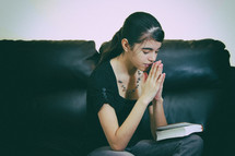teen girl sitting on a couch praying
