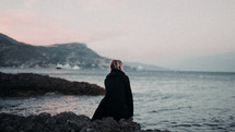 a woman sitting on a rocky shore in a coat