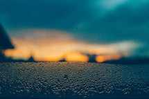 Sunrise through raindrops on a window