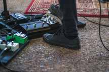 feet on a guitar pedal