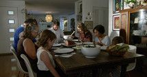 a family saying grace around a dinner table