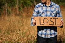 "Man holding ""Lost"" cardboard sign"