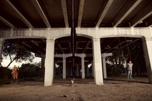 man and woman swinging under  highway