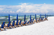 beach chairs and umbrellas on a white sand beach