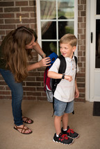 mother getting her son ready for school